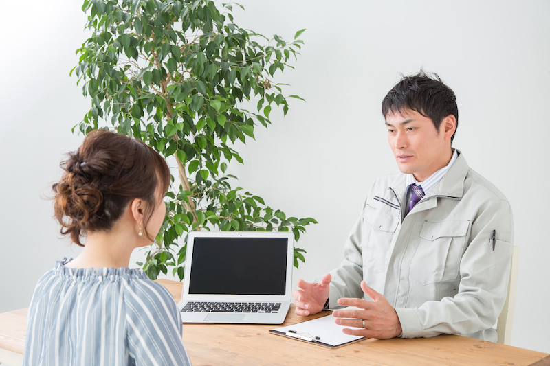 パソコンを使って説明する作業着の男性