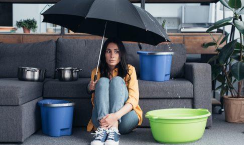 家の中で傘をさす女性