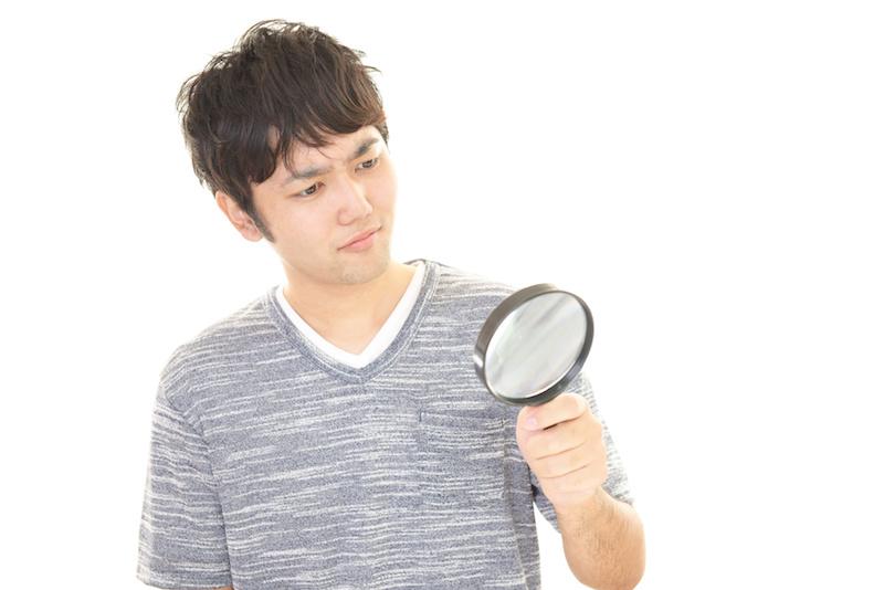虫眼鏡を持って悩む男性