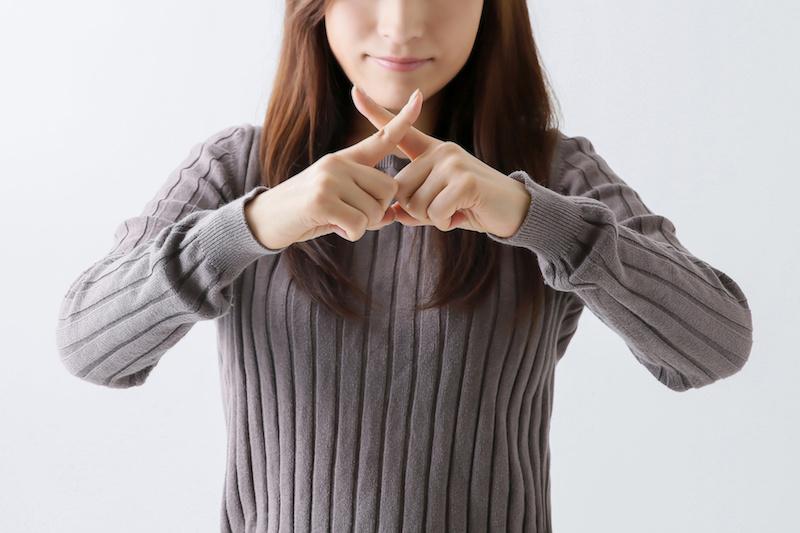 指でバツマークを作る女性