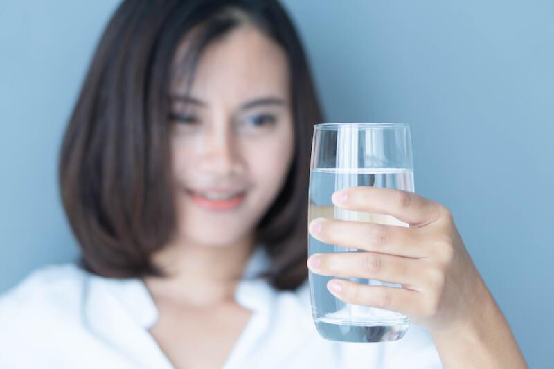 コップの水を見る女性