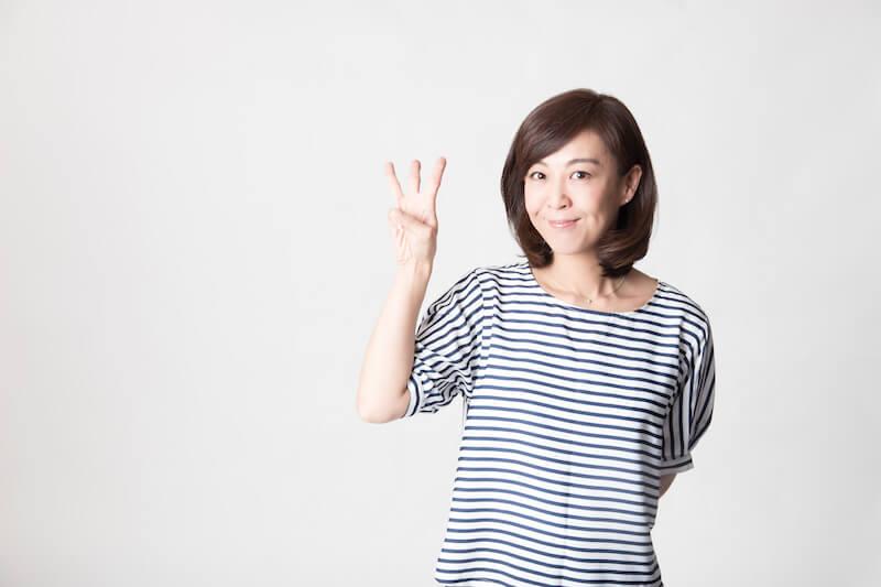 指を3本立てる女性